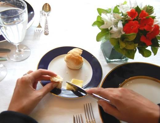 numa mesa de almoço, uma mão segura uma faca e outra segura um pedaço de pão, que está num pratinho. ao lado direito tem um pequeno vaso de flores