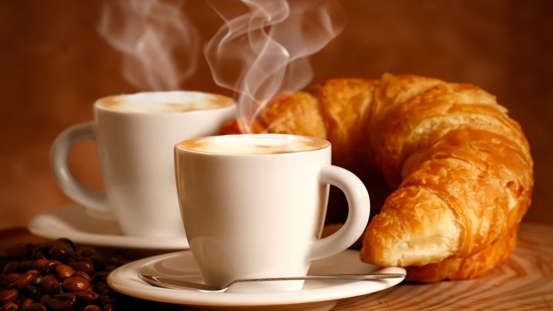 2 Xícaras de café, saindo fumaça ao lado de um croissant, espécie pão folhado e enrolado, servido rechedado ou não.