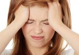 A foto mostra uma mulher jovem fazendo cara de dor.