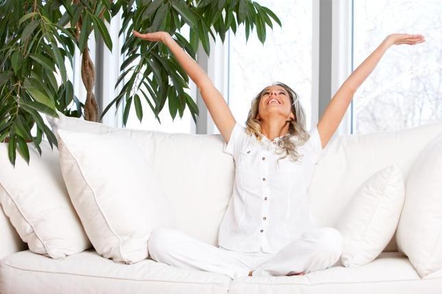 Mulher loira de aproximadamente trinta anos e cabelos longos e calça e camisa de algodão brancas está sentada de pernas cruzadas sobre o sofá também branco. Ela está co os dois braços para cima em uma atitude de alegria sorrindo para o alto.Atrás dela uma planta grande e verde contrasta com o cenário claro da casa iluminada