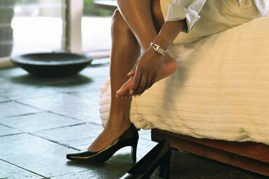 A foto mostra apenas as pernas de uma mulher negra e magra vestindo uma saia executiva bege sentada em uma cama. Ela calça apenas um pé do par de sapatos pretos. O outro pé está descalço e ela massageia a planta do pé com as mãos.