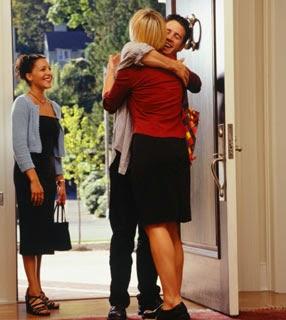 Um homem , vestindo calça preta e cardigan claro, abraça uma mulher loira, usando saia preta e camisa vermelha, junto a porta de uma casa e outra mulher usando vestido preto, olha essa cena.