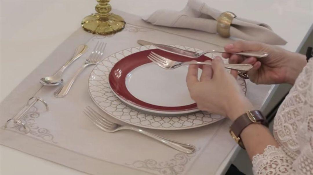 Uma mesa de jantar com toalha cor branca, com prato raso , cor branca, com prato de entrada, com bordas bordô, copos e talheres e copos postados. Uma mão segura um garfo de peixe e uma faca.