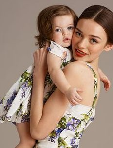 Mulher usa vestido , cor branca, com detalhes em flores roxas e azuis. O modelo usa alças finas. No colo dela, uma pequena menina com o mesmo modelo da mãe.