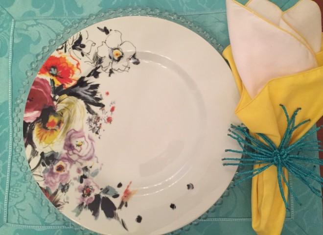 Um prato branco, raso mostra estampa floral desenhada livremente. Flores de campo em cor de vinho, vermelho coral, preto e amarelo - em um buquê campestre estilizado que ocupa apenas um terço da circunferência do prato. Ele esta sobre um souplat em vidro transparente e um jogo americano turquesa com guardanapo amarelo e branco seguro por um porta guardanapos arrematado por um pingente de miçangas turquesa. A idéia é de uma mesa alegre e remete a um frescor - proporcionado principalmente pelo toque de turquesa do jogo americano