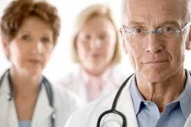 Imagem de rostos de um médico com estetroscópio no pescoço e logo atras outras duas médicas com uniforme e estetroscopio.
