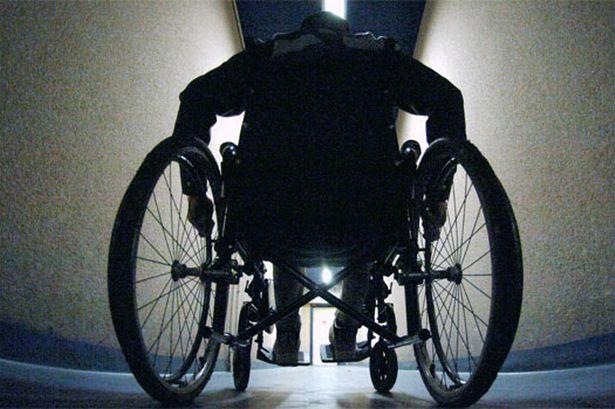 Imagem de um corredor de hospital, com um pessoa andando numa cadeira de rodas