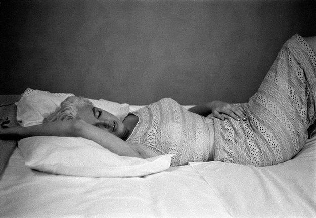 a atriz Marilyn Monroe está deitada em dormindo em uma foto em preto e branco com o braço direito sobre a cabeça em uma atitude de abandono e conforto.
