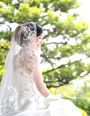 mulher japonesa, ela está sentada num jardim, usando vestido de noiva.