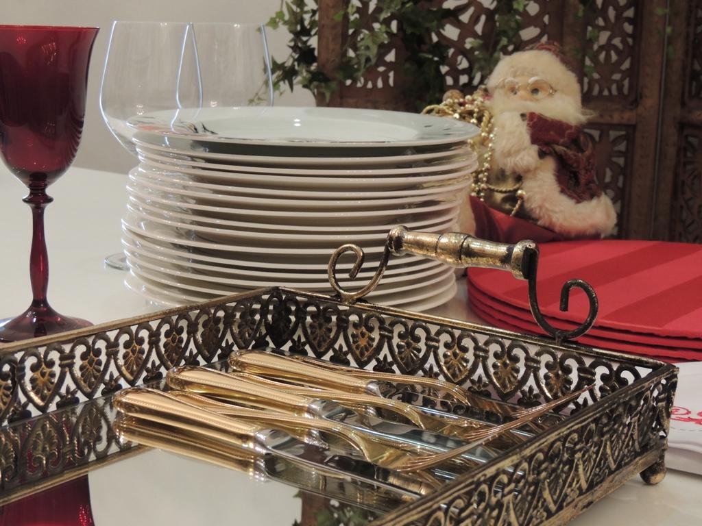 talheres sobre uma bandeja de prata trabalhada e ao fundo uma pilha de pratos