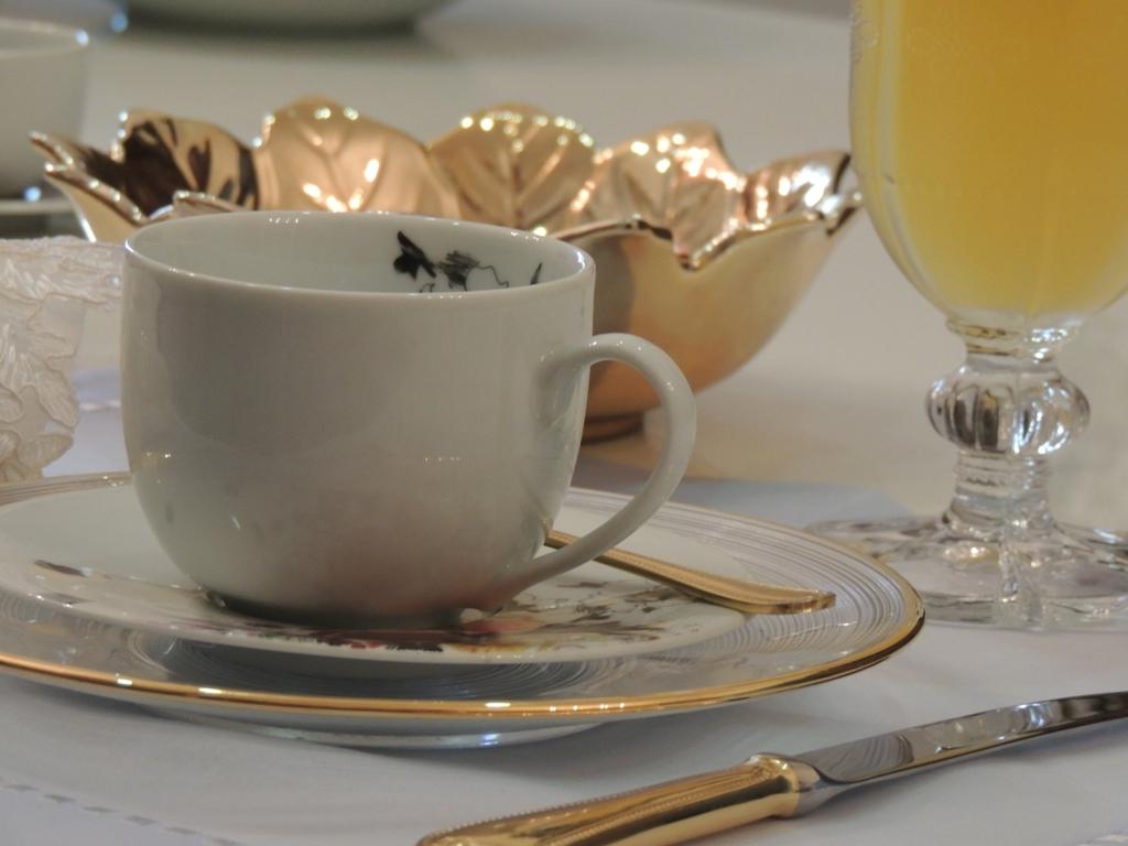 sobre uma mesa, com toalha branca, uma xícara de chá, de porcelana branca, com um detalhe floral na parte interna, sobre um pires com detalhes floral na borda, ao fundo um copo de vidro, com suco de laranja e um pote dourado. Em primeiro plano , uma faca com cabo dourado.