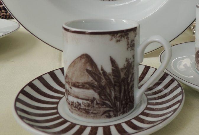 Coleção de porcelana Schmidt, linha Francesca Romana, ao fundo um prato fundo, com figura da Lapa do Rio de Janeiro em sépia, a frente xicaras de cafe e xícara de chá, com imagens o Rio de Janeiro em sépia.