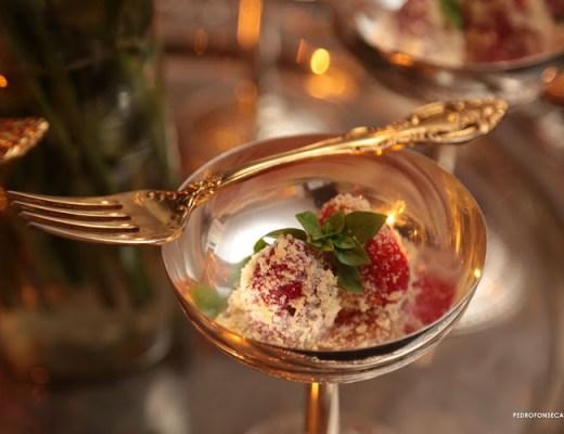 Taça dourada, e um garfo cruzado sobre a borda da taça. Dentro , morangos com uma cobertura de queijo, mel e pimenta.