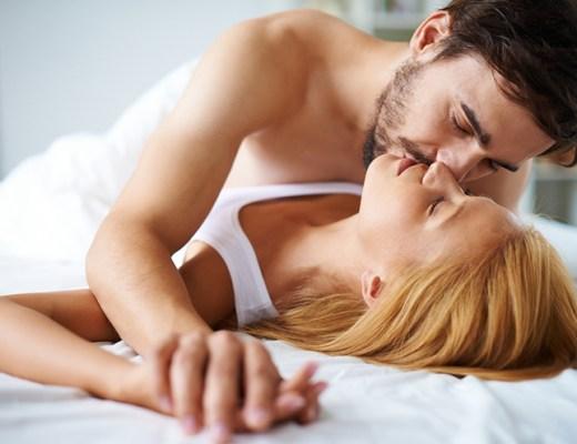 Casal jovem, deitados numa cama. Ele está perto dela, sem camiseta, ela é loira, usa camiseta branca, com alça e está deitada e estão abraçados.