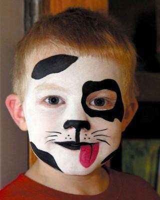 Menino com o rosto pintado como uma cachorro dálmata. A pele está pintada de branco, com detalhes em preto em volta do olho, na testa, no queixo. O nariz e a boca também estão pintados de preto com uma língua vermelha para fora da boca