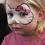 menina pintada com a mascara da gatinha Hello Kitty.