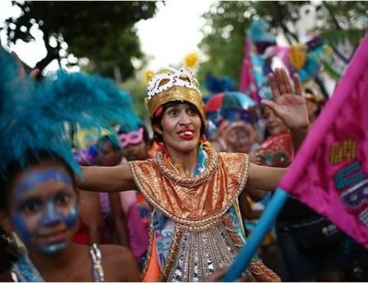 folião usando fantasia muito colorida , em tons dourado alaranjado , chapéu com máscara na cor branca, junto aos outros foliões usando plumas azuis na cabeça. muitos guarda-chuvas coloridos.