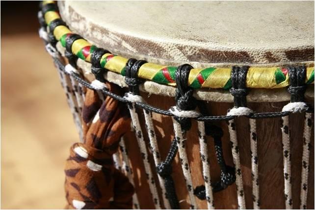imagem de um atabaque de couro e madeira, com adriças coloridas e cordas para afinação.