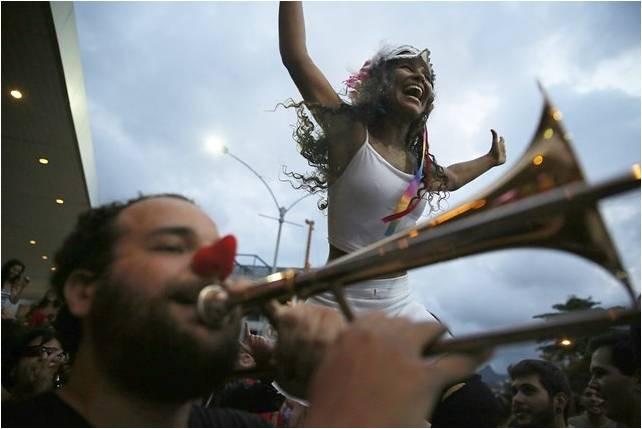 foliões de bloco de rua, um homem com nariz de palhaço toca trombone de vara e uma mulher sorri, com os braços abertos usando top branco com alcinhas, ela usa uma máscara sobre a testa.