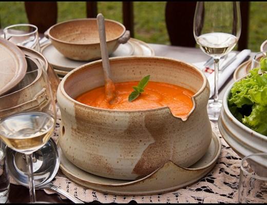 mesa de jantar, tendo ao centro uma sopeira em cerâmica, com creme de abóbora, outros detalhes decoração a mesa. verduras, taças.