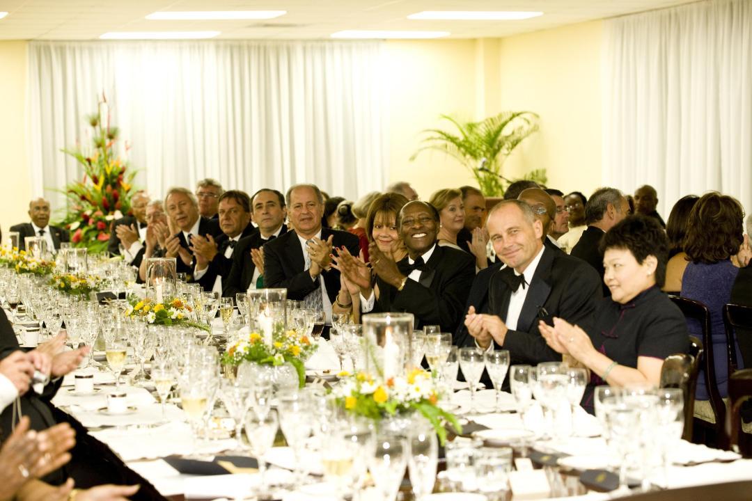 Uma grande mesa de jantar completa, com embaixadores e diplomatas usando black-tie, todos aplaudem.