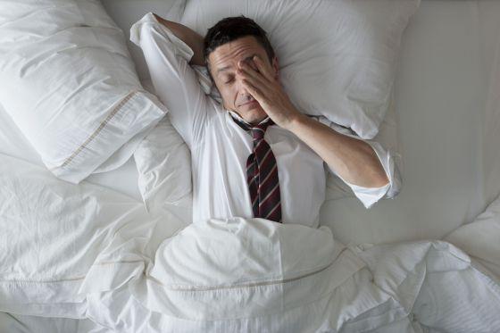 homem deitado na cama, acordando, porém com camisa social , cor branca e gravata , quadriculada, em tons vermelho e preto.