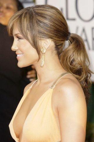 atriz Jennnifer Lopez, de imagem lateral, com cabelos castanhos, presos (rabo de cavalo) e um vestido em tom nude, com decote acenturado. Usa brincos dourados , tipo pingente.