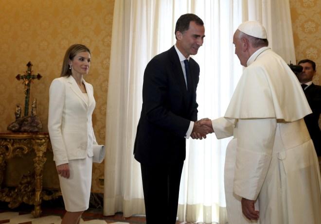 Papa Francisco em seu gabinete da Biblioteca do Vaticano, recebe o Rei Felipe da Espanha , usando terno escuro e faz reverência a Sua Santidade, e logo atrás a Rainha Letízia, usando conjunto branco.