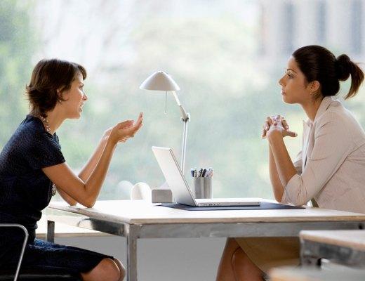 Num escritório de empresa, Uma mulher veste conjunto azul escuro, está sentada junto a uma mesa e conversa com sua interlocutora que usa cabelos presos (rabo de cavalo) e usa conjunto rosa claro e ambas estão com os braços debruçados sobre a mesa.