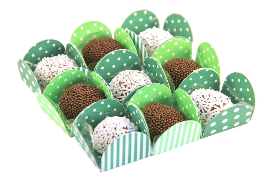 nove formas coloridas em tons verdes contendo brigadeiros feitos com biomassa de banana verde. Alguns em chocolate branco e outros em chocolate normal.