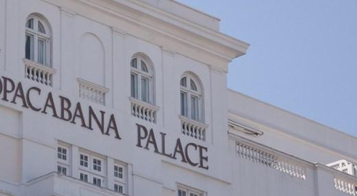 Imagem da fachada superior do hotel Copacabana Palace no Rio de Janeiro, totalmente na cor branca e as letras do nome do hotel e enormes letras na cor marrom escuro.