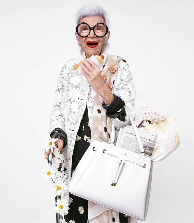 Iris Apfel, uma senhora de mais de 80 anos em foto de meio corpo usando grandes óculos redondos e uma calça e blusa pretas com uma capa de renda branca por cima e uma maxi bolsa branca e muito moderna mostrando que a elegância não tem idade