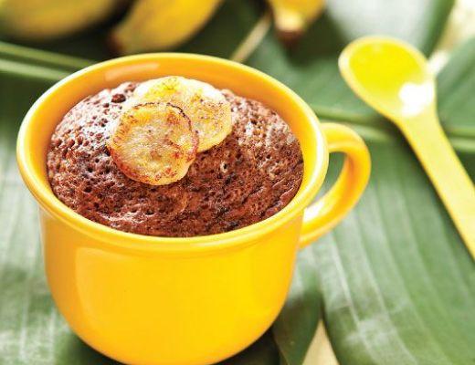 Uma caneca amarela com um bolo de chocolate de aspecto apetitoso está sobre uma folha de bananeira verde com bananas amarelas ao fundo.