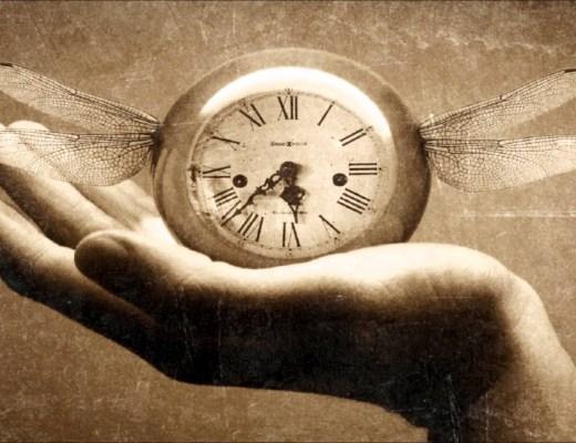 Uma mão em primeiro plano em foto sépia segura um relógio antigo de numeros romanos com asas que parecem asas de libélulas.