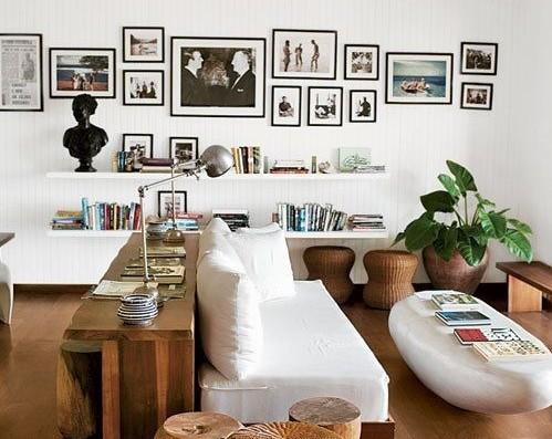 Foto de uma sala de estar com piso em madeira e paredes brancas onde se vê um sofá branco no centro e um banco igualmente branco em formato oval que serve de mesa de centro. Nas paredes brancas quadros com molduras leves escuras estão pendurados complementando o efeito de leveza e espaço.