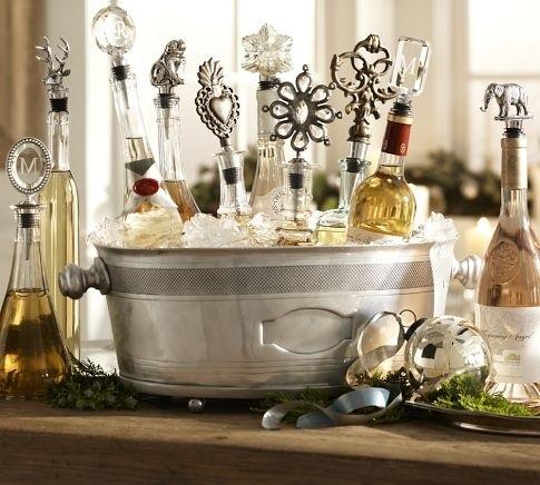 Várias garrafas de bebidas, dentro de um balde de prata, com muito gêlo. Cada garrafa tem uma rolha diferente.