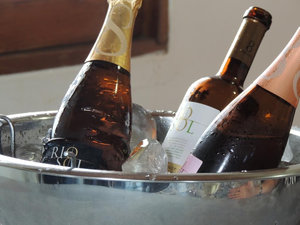 Num balde de gelo, tres garrafas de vinhos estão gelando, todas sem rolha, e o balde de prata.