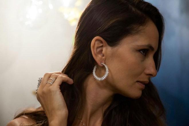 modelo de longos cabelos castanhos está de perfil exibindo um brinco de argola de diamantes.
