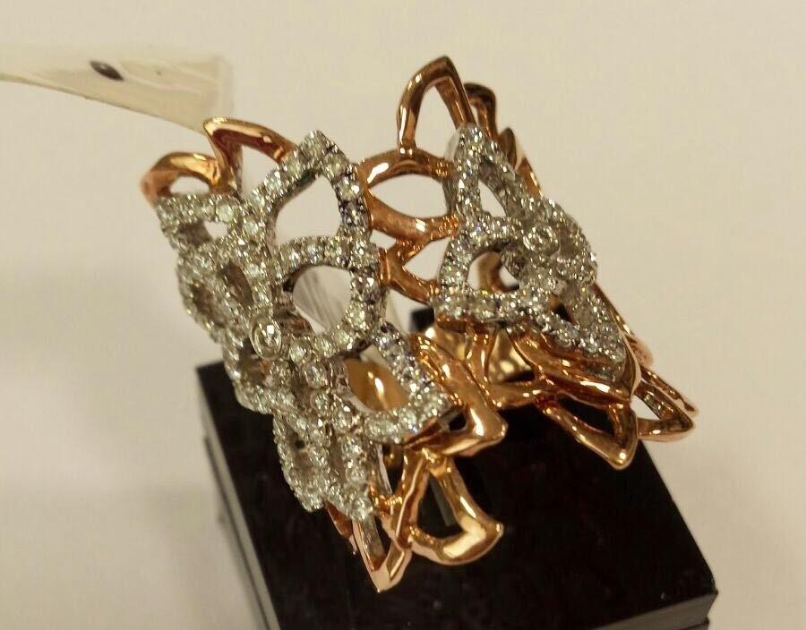 anel em ouro branco e ouro amarelo trabalhado com formas orgânicas enlaçadas umas nas outras e com acabamento de brilhantes