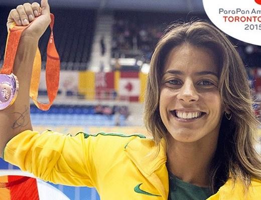 A beira de uma piscina olimpica a nadadora Letícia da seleção brasileira de Natação, ergue seu braço direito que segura nas mãos uma medalha - Ela está sorrindo, cabelos loiros lisos e soltos