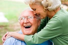 Um casal de aproximadamente 70 anos se abraça rindo aparentando grande felicidade e cumplicidade. Ele de óculos e careca com camisa azul clara ela com uma malha verde clara e cabelos brancos arrumados na altura dos ombros.