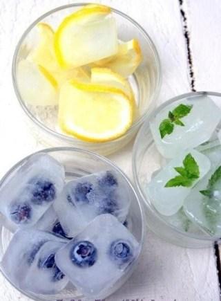 Uma foto em close tirada de cima de 3 copos. Em dois deles estão pedras de gelo colorido. Um com gelo recheado de pétalas de hortelã e o outro com gelo com pétalas de violetas azuis. O terceiro copo tem fatias finas de limão siciliano e gelo.