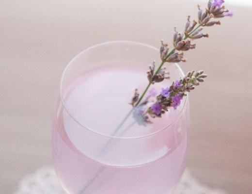 Uma taça apoiada em um pires branco com um líquido em tom roxo clarinho tem uma flor de lavanda dentro como se fosse uma colher para mexer