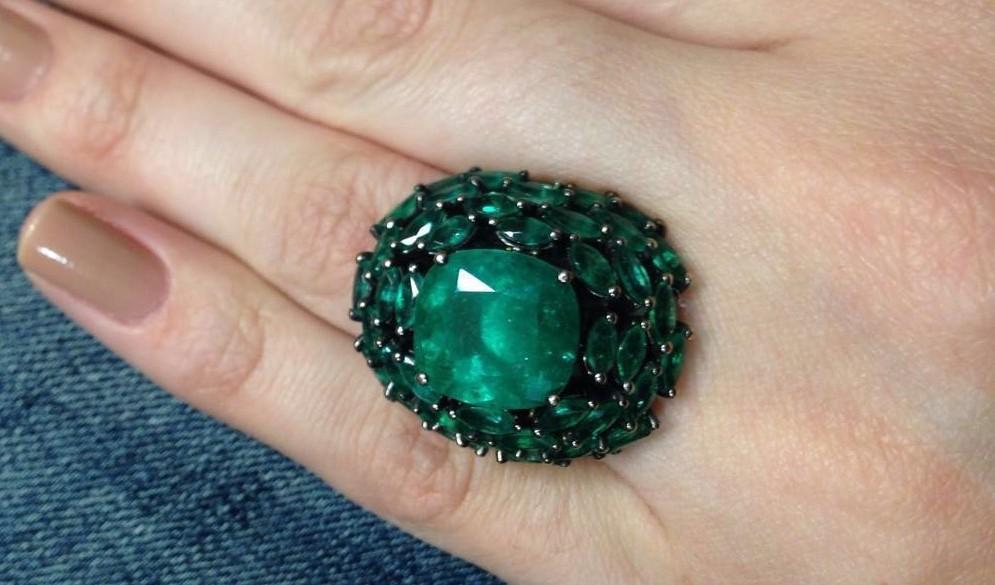 uma mão de mulher está em close usando um anel de pedra esmeralda verde oval rodeado por três fileiras de esmeraldas pequenas em formato de losango. A aparência é de uma jóia antiga e muito valiosa
