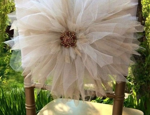 a foto mostra uma cadeira em madeira escura com uma flor de tule branco em tamanho gigante amarrada a seu encosto. No centro da flor um miolo de sementes no mesmo tom da madeira da cadeira compõem o arranjo.