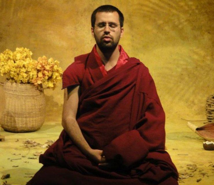 Lama Michel Rimpoche, monge budista, jovem, magro, cabelos raspados, sentado na posição de seiza, medita num templo florido, usando os mantos marsala, simbolos desta religião. Está de olhos fechados.