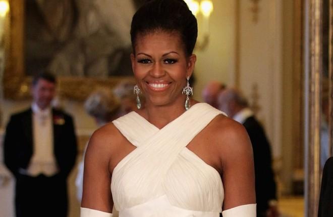 Michelle Obama veste um modelo de vestido branco sem ombro mas com alças largas cruzadas na frente. Sua pele negra contrasta com o tom creme claro do tecido e ele está de cabelo preso em um coque clássico.