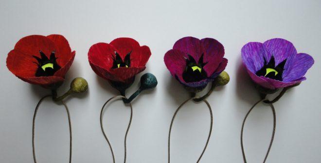 flores em papel crepom , coloridas, na imagem estão 4 flores , nas cores vermelha, roxa clara e pink. Tendo como suporte um barbante