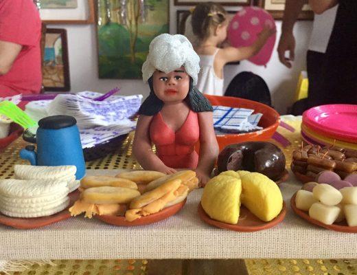 Mesa de festa, com pequenos pratos, com várias comidas típicas brasileiras. e ao centro tem uma imagem das namoradeiras , em barros.