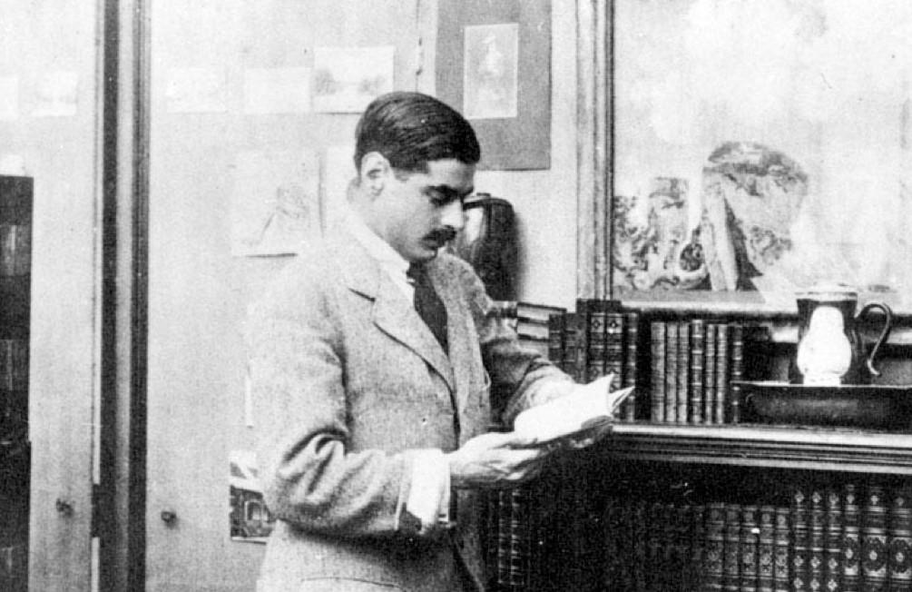 Imagem de namorado de Coco Chanel - Senhor Arthur Capel - usando terno claro junto a um móvel com livros.